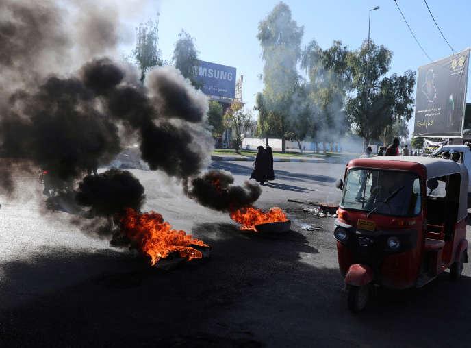 Des manifestants brûlent des pneus pour bloquer la route à Kerbala, en Irak, le 23décembre.