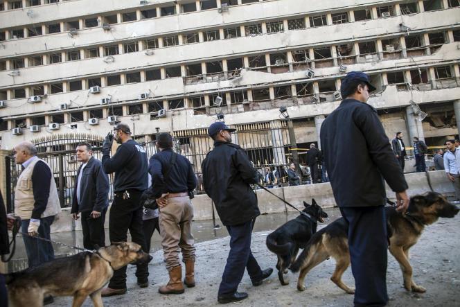Des policiers égyptiens accompagnés de chiens après l'explosion d'une voiture piégée au Caire, le 24 janvier 2014.