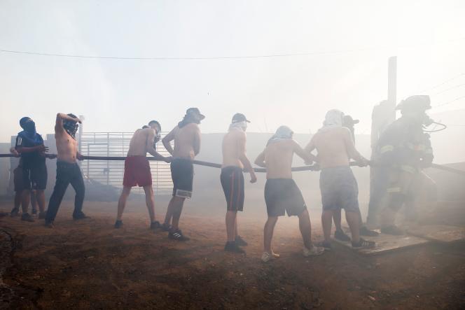 Un pompier aidé de civils tentent d'éteindre un feu à Valpariso, le 24 décembre.
