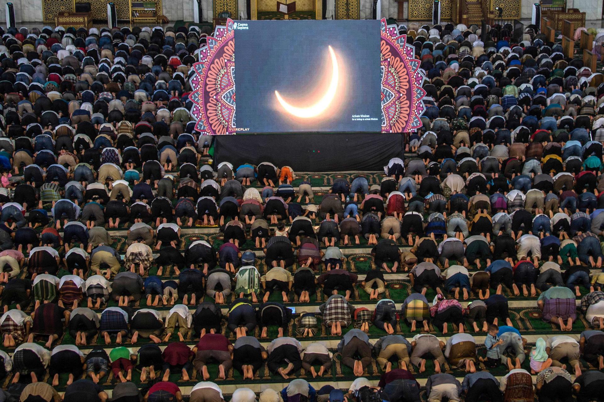 Des personnes prient devant la retransmission de l'éclipse, àSurabaya (Indonésie), le 26 décembre.