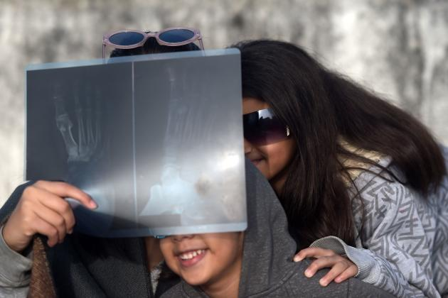 Des enfants observent l'éclipse à travers une radio à Islamabad, au Pakistan.