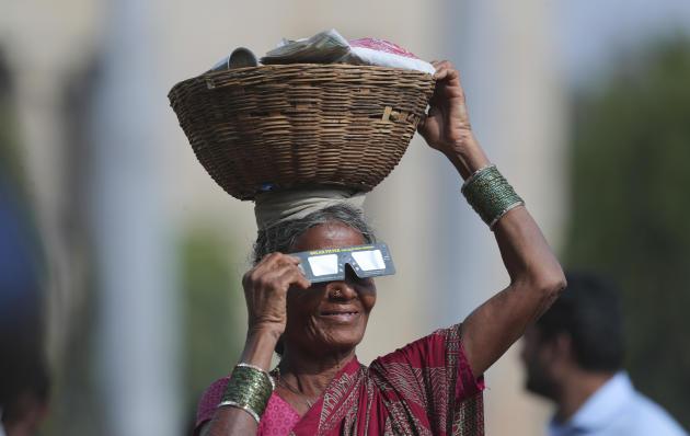 Un vendeur de rue observe l'éclipse à Hyderabad, en Inde.