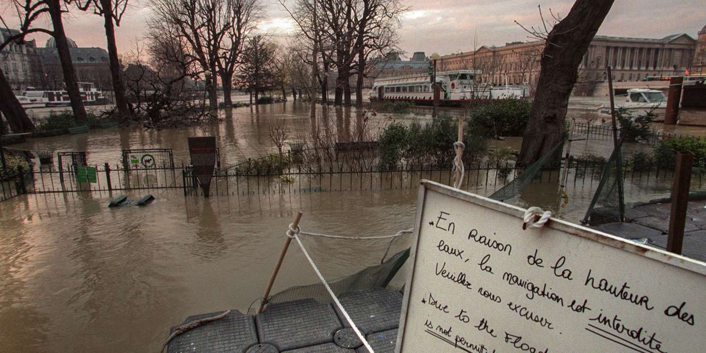 (FILES) In this file photograph taken on December 29, 1999, a sign at the entrance of a flooded park alerts visitors that navigation on the River Seine from Ile de la Cite in Paris, is forbidden after a storm blasted its way across France and other European countries, with record breaking 175-kilometre-per-hour (108-mile-per-hour) winds.     The winter storms