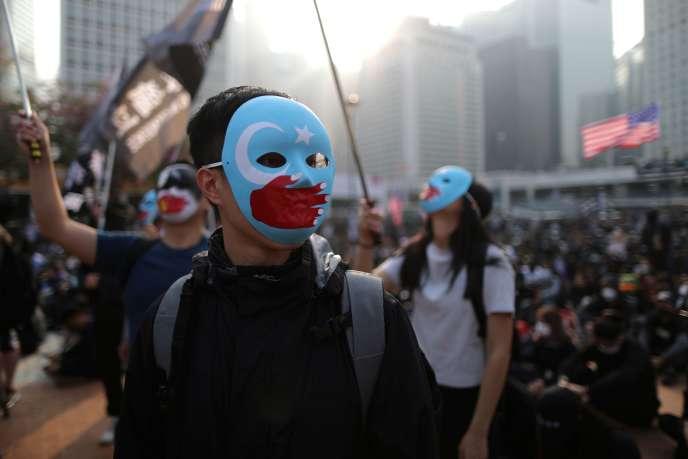 Des manifestants à Hongkong portent des masques de soutien aux Ouïgours, le 22 décembre.