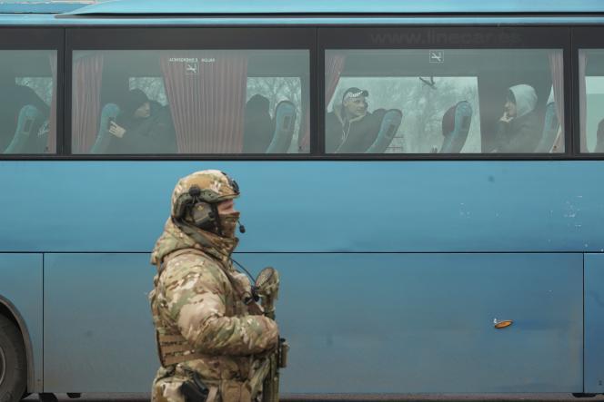Un soldat ukrainien en faction à côté d'un bus dans lequel attendent des séparatistes du Donbass, le 29 décembre.