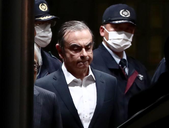 Carlos Ghosn, l'ancien président-directeur général de l'Alliance Renault-Nissan-Mitsubishi, est escorté alors qu'il sort de prison à Tokyo après sa libération sous caution, le 25avril2019.