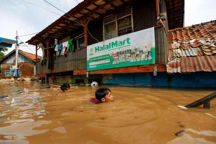 Des habitants de Djakarta tentent de récupérer des objets de leur maison, inondée après les fortes pluies enIndonésie, le 2janvier.