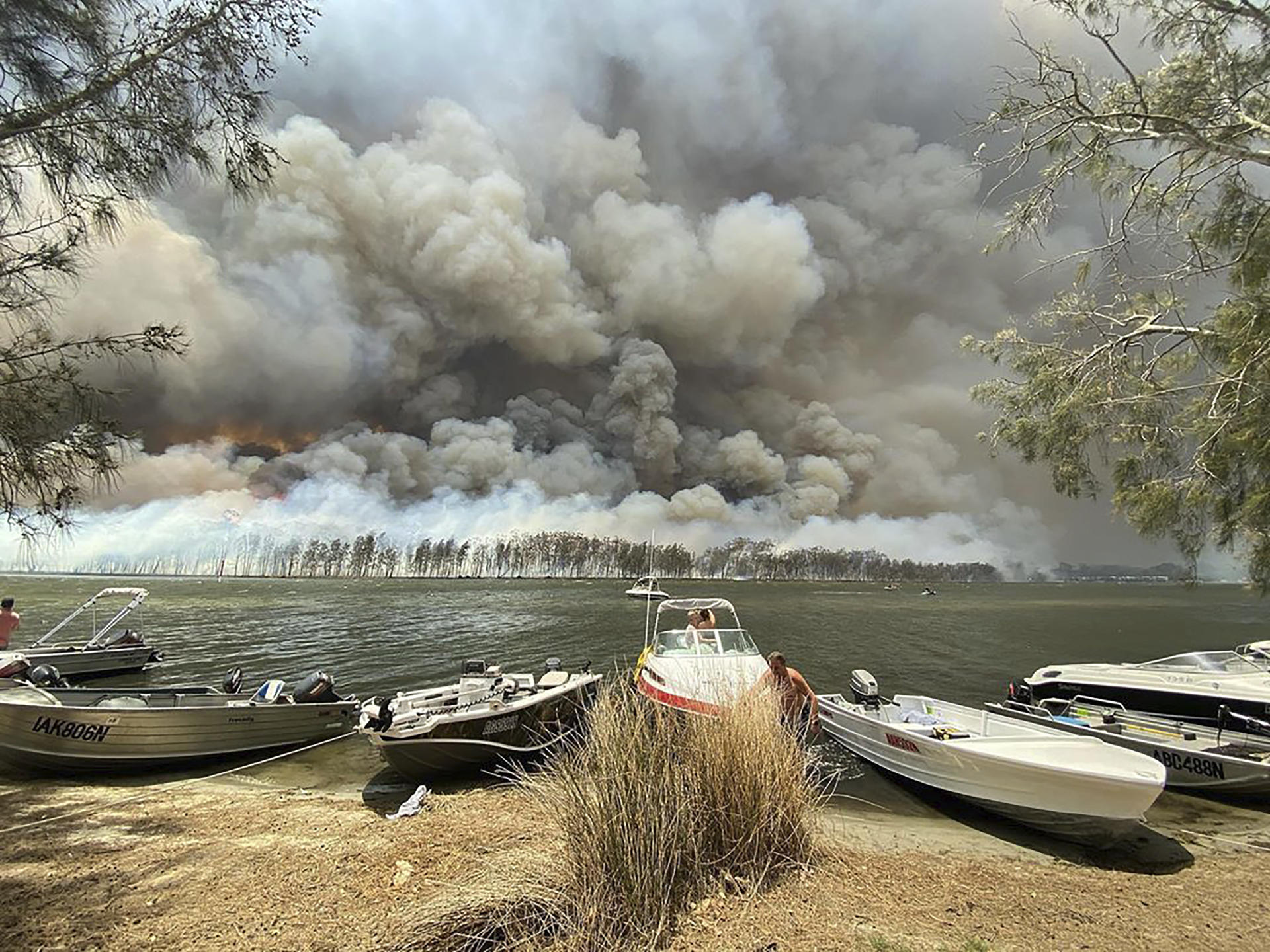 Des bateaux sont amarrés alors que les incendies de forêt font rage derrière le lac Conjola, Australie, le jeudi 2 janvier.