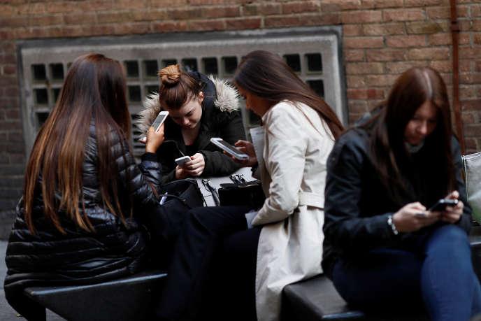 Des femmes consultent leurs portables, à Londres, le 6 octobre 2016. Avec le Brexit, les factures téléphoniques pourraient augmenter.