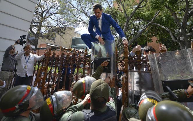 Juan Guaido grimpe la clôture dans une tentative infructueuse d'entrer dans l'enceinte de l'Assemblée, à Caracas, le 5 janvier.