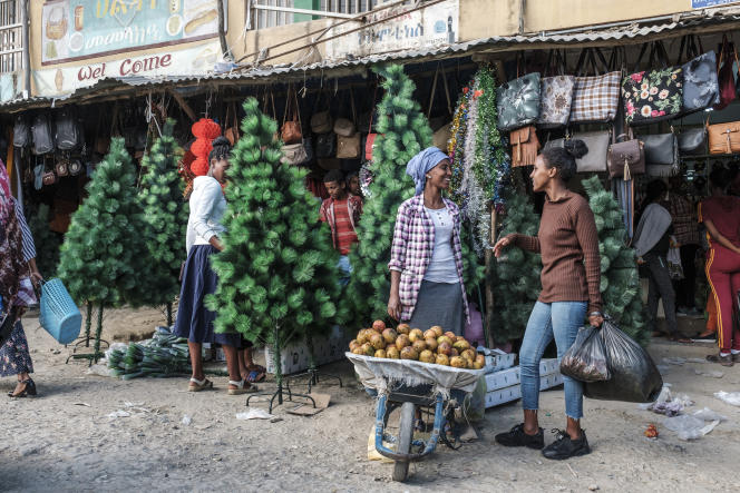 Une vendeuse de mangues devant un magasin proposant des sapins de Noël, à Mekelle, en Ethiopie, le 4janvier 2020.