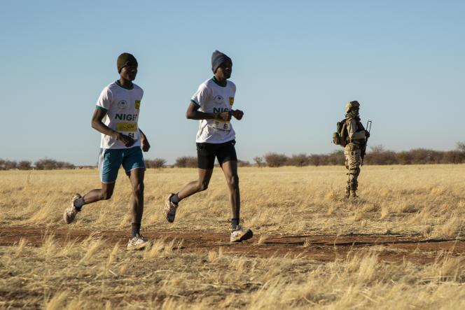 Deux participants au Grand Marathon du Ténéré passent devant un soldat sécurisant l'épreuve, près d'Agadez, au Niger, le 29décembre 2019.