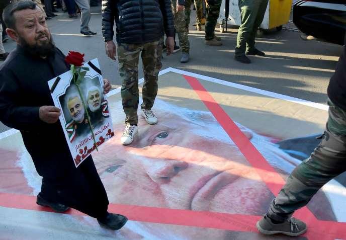 Des Irakiens marchent sur le portrait de Trump lors d'une cérémonie d'hommage au général iranien Soleimani, à Bagdad, le 6 janvier.