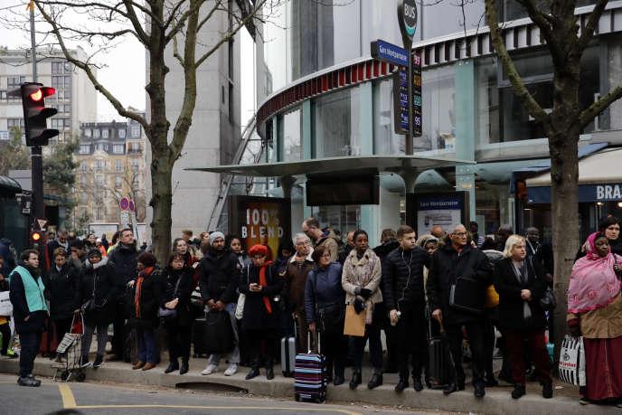 Des usagers attendent leur bus à Paris, mardi 7 janvier.