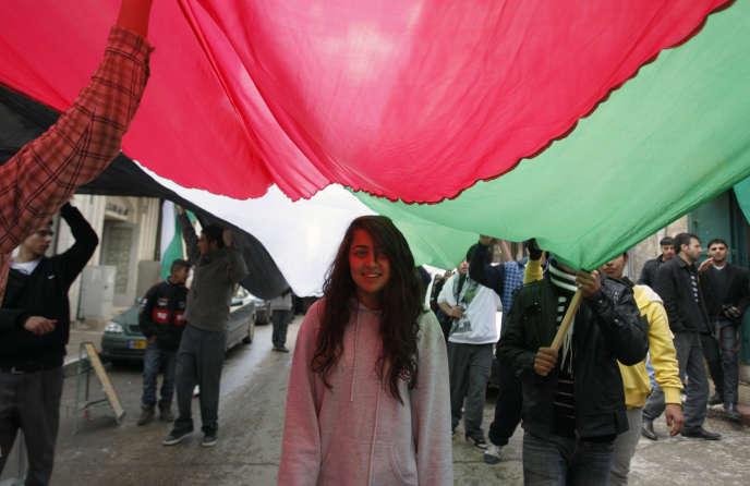 Une jeune fille palestinienne sous un drapeau lors d'une manifestation à Ramallah, en Cisjordanie, en 2011.