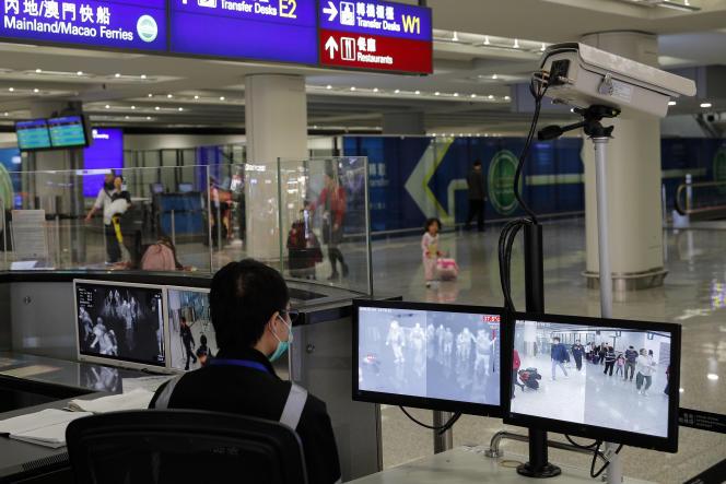 Surveillance électronique de la température des passagers par des agents du service de santé à l'aéroport de Hongkong, le 4 janvier.