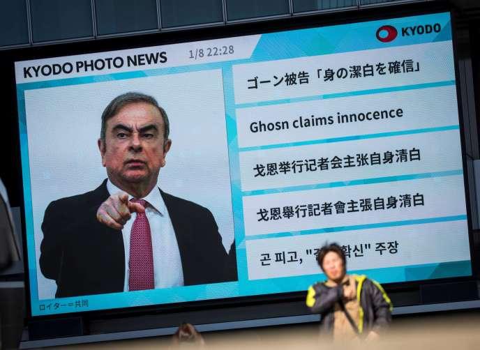 Un piéton passe devant un grand écran montrant une émission d'actualités mettant en vedette l'ancien chef de Nissan Carlos Ghosn à Tokyo le 9 janvier 2020. Le ministre japonais de la Justice a exhorté Carlos Ghosn à revenir et à plaider sa cause devant le tribunal, après que l'ancien magnat de l'automobile a fuit au Liban.