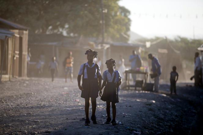 Deux fillettes sur le chemin de l'école à Canaan, un quartier deCroix des Bouquets, à Haïti, créé pour les personnes qui ont perdu leurs maisons lors du tremblement de terre, il y a dix ans.