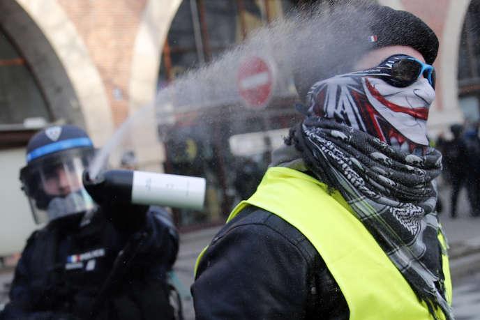 Un policier pulvérise du gaz lacrymogène sur un manifestant ayant revêtu un gilet jaune lors d'une manifestation contre la réforme des retraites, le11janvier2020, à Paris.