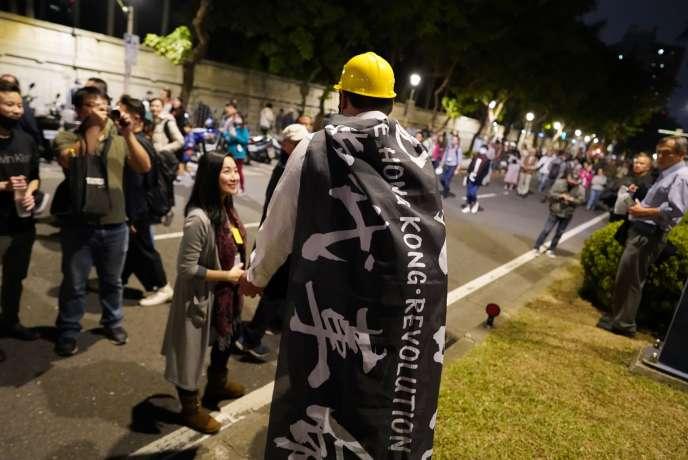 Une personne porte un drapeau de soutien à Hongkong lors du grand rassemblement de soutien à la présidente taïwanaise, Tsai Ing-wen vendredi, 10 janvier à Taipei.