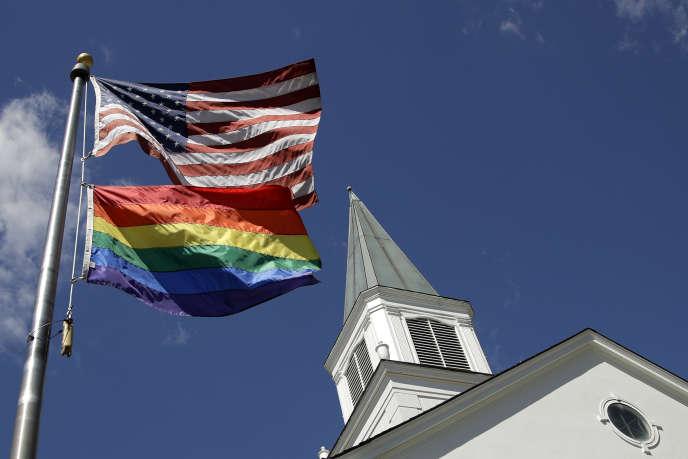 Un drapeau de la fierté gay flotte avec le drapeau américain devant l'église méthodiste unie d'Asbury, à Prairie Village (Kansas), en 19 avril 2019.