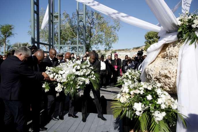 Le président d'Haïti Jovenel Moïse et des représentants étrangers portent un bouquet de fleurs, à Titanyen le 12 janvier 2020, pendant la cérémonie de commémoration du dixième anniversaire du tremblement de terre.