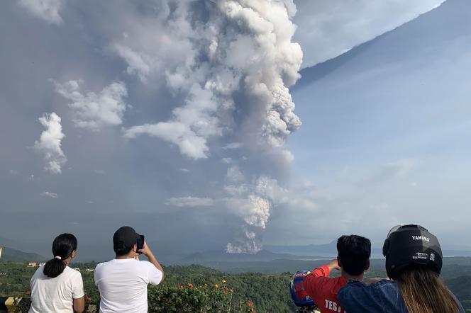 Des habitants photographient le nuage de cendres qui s'échappe du volcan Taal, depuis la ville de Tagaytay, le 12 janvier.