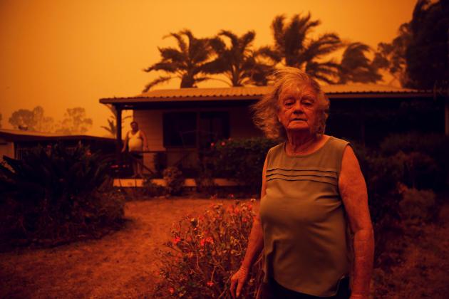 Nancy Allen devant sa maison à Nowra, alors que les vents poussent la fumée et les cendres de l'incendie Currowan vers la région, le 4 janvier.