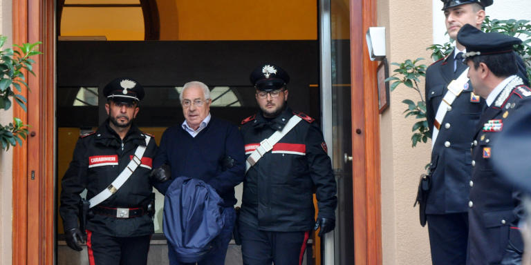 Settimino Mineo (C), jeweller and new head of the Sicilian mafia, is escorted by carabinieri as he exits a police station after his arrest, in Palermo on December 4, 2018. - Italian police have arrested new Mafia boss Settimino Mineo and dozens of other suspects in a major swoop, officials and media said on December 4. Police arrested jeweller Mineo, 80, and 45 others in Sicily just before he was due to be officially anointed at a reconvened Mafia Commission or Cupola, the police said. (Photo by Alessandro FUCARINI / AFP)