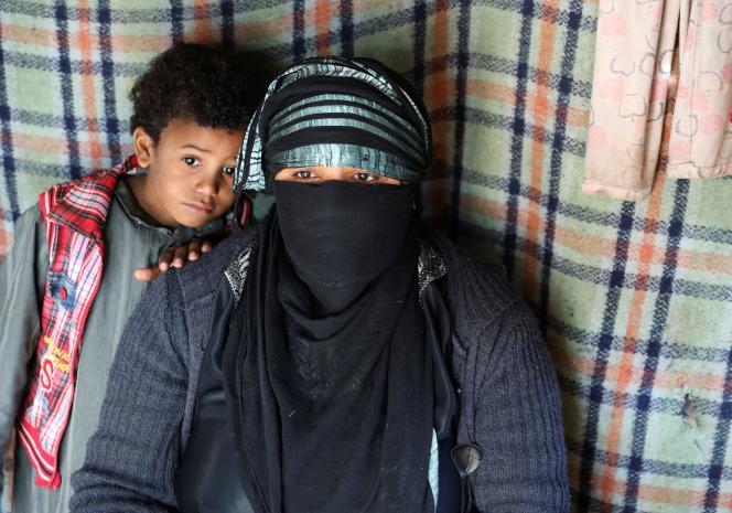 Sameera Hussein Nasser, 40 ans, avec l'un de ses fils, dans le camp de personnes déplacées où elle vit près de Sanaa, au Yémen, le 21 décembre 2019.