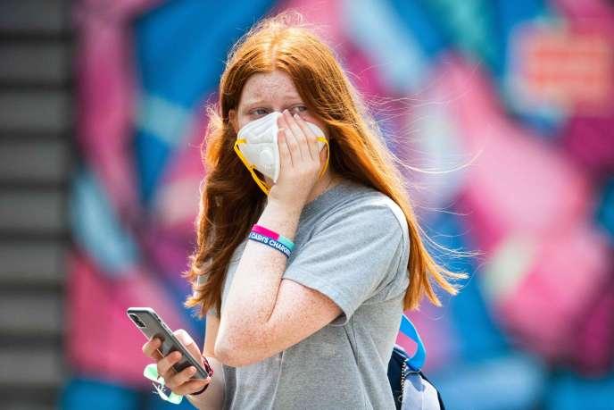 Une femme tient un masque sur son visage pendant les séances d'entraînement de l'Open de tennis d'Australie, à Melbourne, le 15janvier.