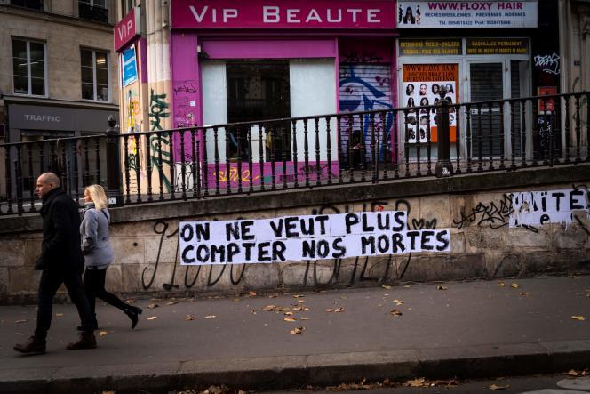 25 novembre 2019, des personnes passent devant une bannière portant l'inscription «On ne veut plus compter nos mortes» dédiée à la mémoire des femmes tuées par un partenaire actuel ou ancien compagnon.