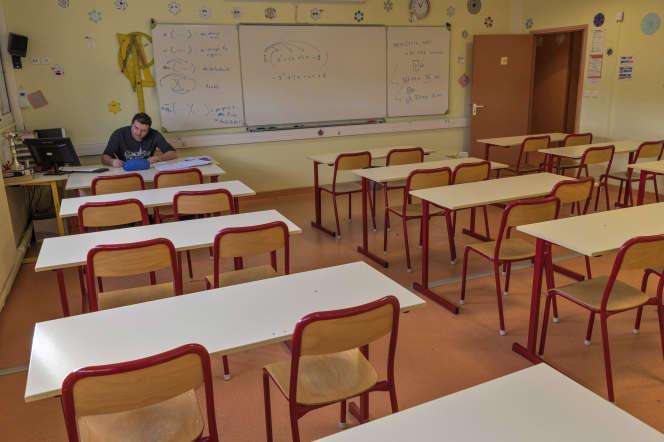 Un professeur de mathématiques corrige des copies dans un collège de Lapalisse (Allier), en décembre 2019.