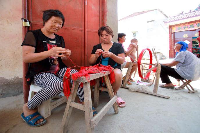 Des Chinoises cousent et tissent sur le pas de leurs maisons, dans le village de Gangchalou, dans la province du Henan, en septembre 2016.