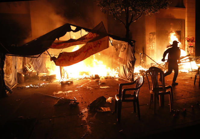 Des manifestants anticorruption tentent d'éteindre l'incendie de leurs tentes, samedi 18 janvier à Beyrouth, au Liban.