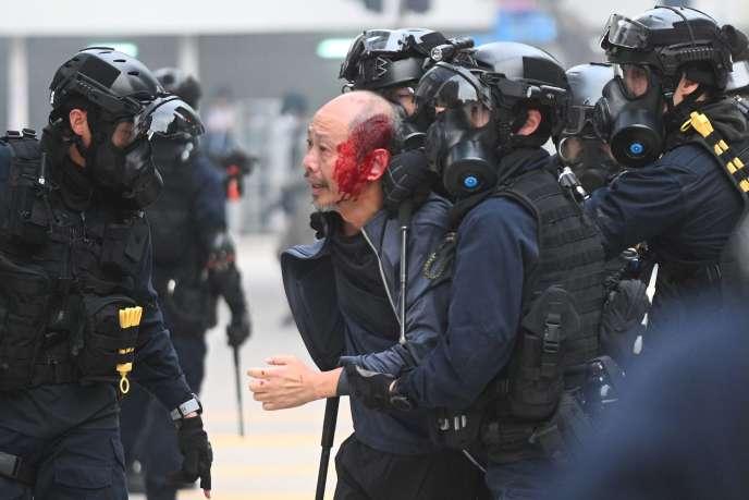 La police interpelle un homme blessé après que les forces de l'ordreont dispersé une foule rassembléeau Chater Garden à Hongkong le 19 janvier 2020.