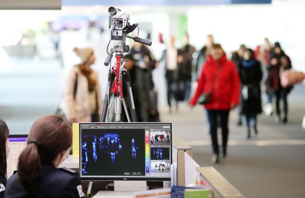 A Séoul (Corée du Sud), les voyageurs à l'arrivée sont scannés par un moniteur thermique.