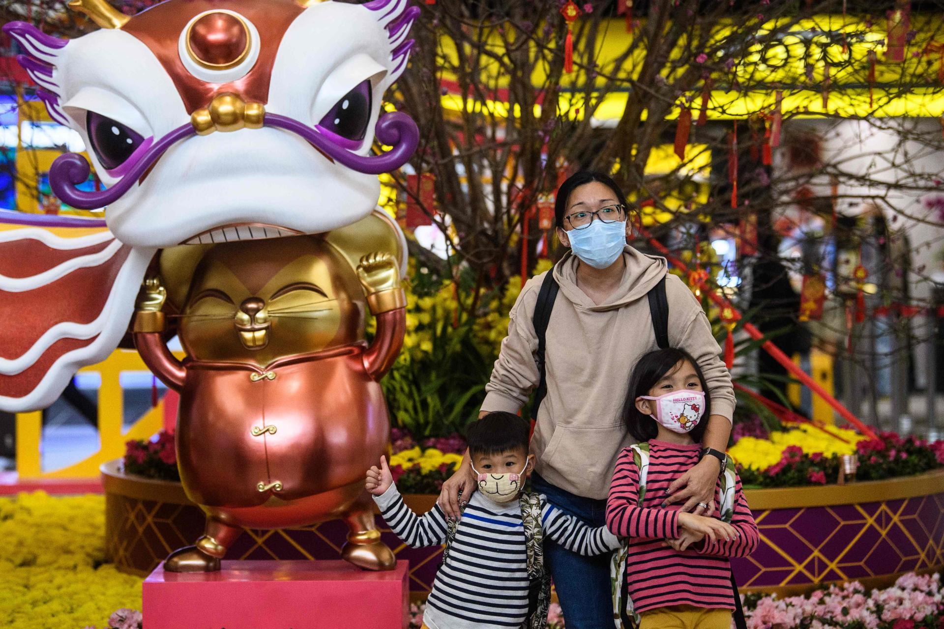 Des voyageurs prennent la pose en famille devant l'installation en vue du Nouvel An à l'aéroport international de Hongkong.