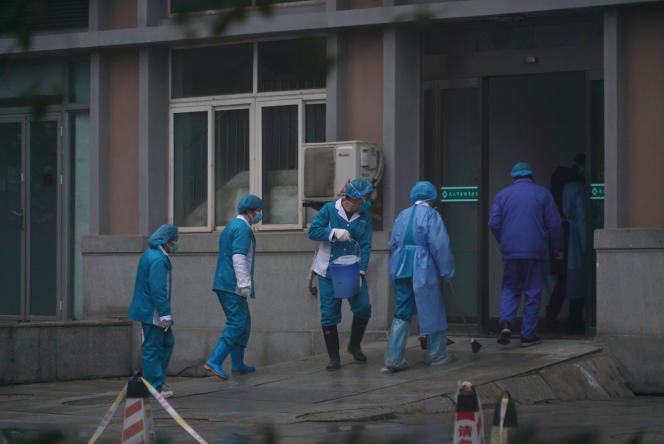 Des employés désinfectent l'entrée de l'hôpital de Wuhan, où des patients contaminés par le virus sont traités, le 22janvier.