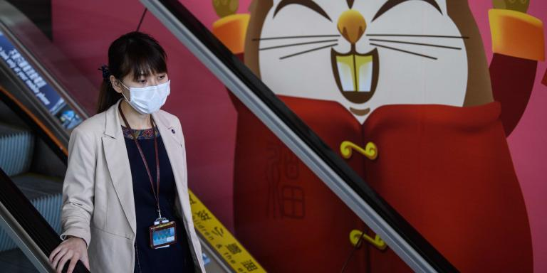 A woman wears a face mask as she takes an escalator past a caricature of a Lunar New Year rat at Hong Kong's international airport on January 22, 2020, after China recently confirmed human-to-human transmission in the outbreak of the new SARS-like virus. A new virus that has killed nine people, infected hundreds and already reached the United States could mutate and spread, China warned Wednesday, as authorities scrambled to contain the disease during the Lunar New Year travel season.  / AFP / Anthony WALLACE