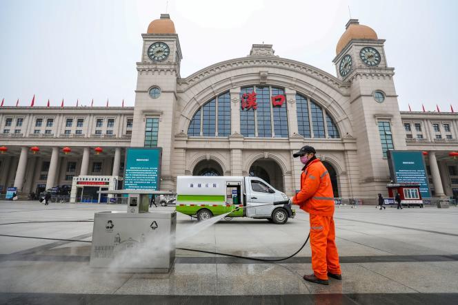 Un employé désinfecte le parvis de la gare de Hankou, à Wuhan, le 23 janvier.