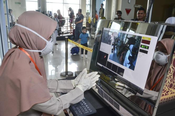 Les passagers sont scannés pour vérifier leur température, à l'aéroport dePekanbaru, sur l'île de Sumatra, en Indonésie.