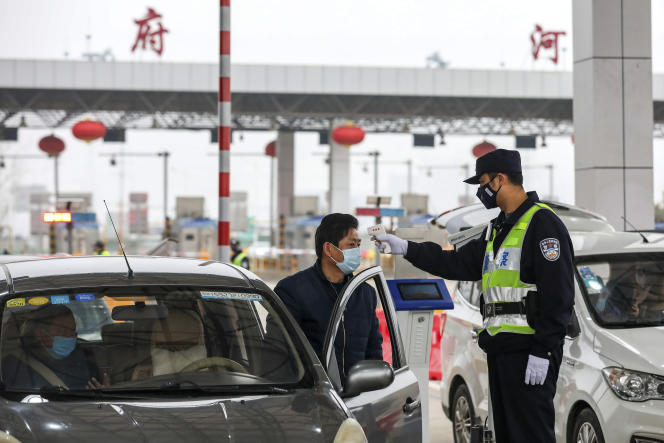 A Wuhan, un policierprend la température d'un automobiliste avecun thermomètre sans contact, le 23 janvier.
