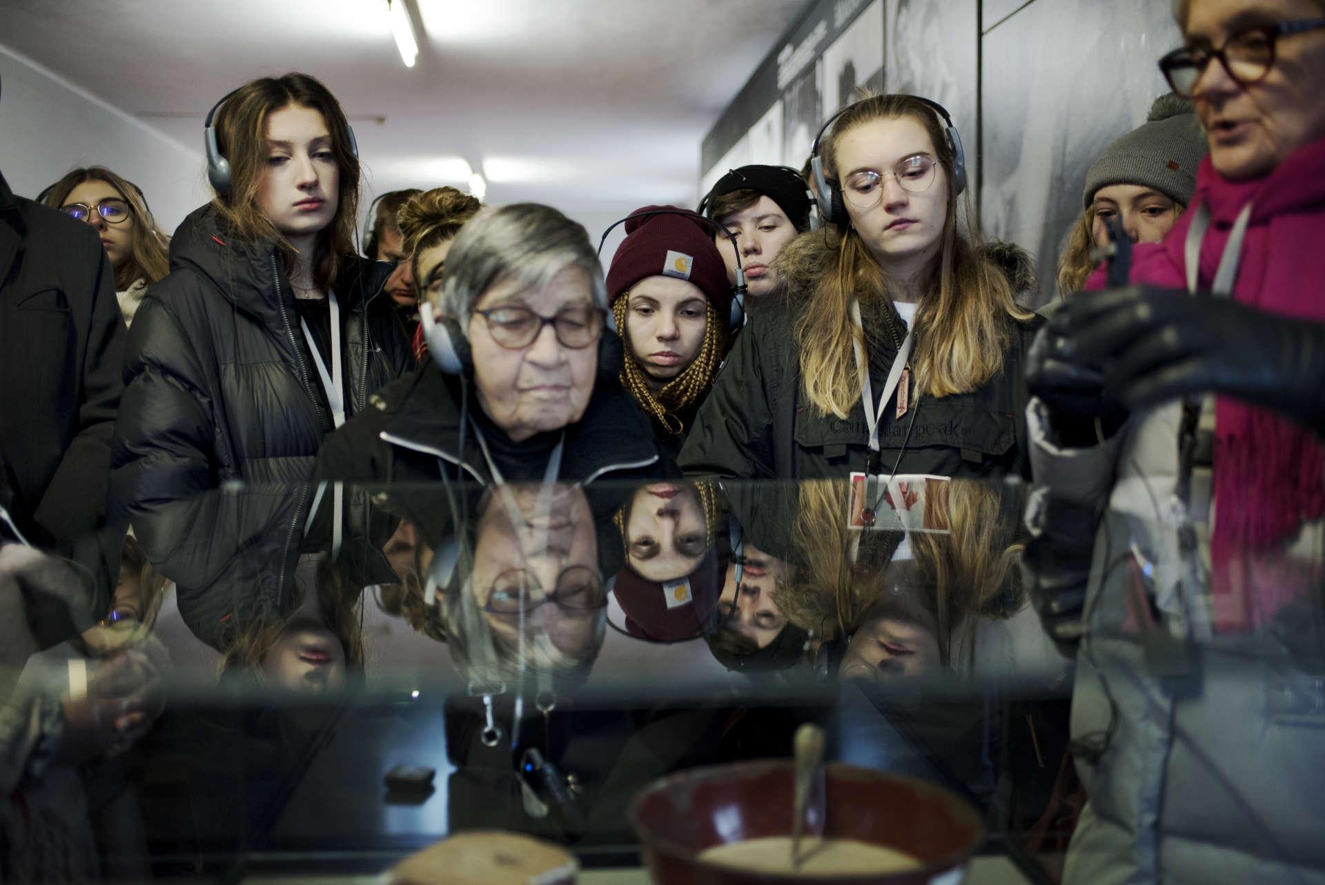 Les élèves et Ginette Kolinka regardent les écuelles dans lesquelles les déportés mangeaient, à Auschwitz. Les rations étaient calculées par les nazis pour une survie entre un et six mois.