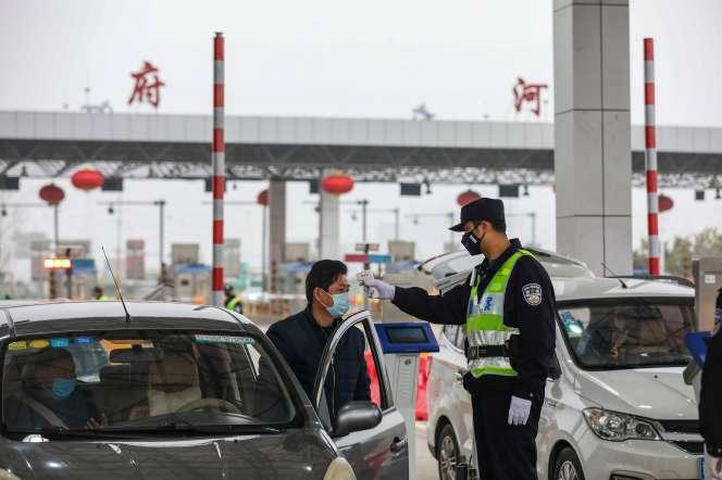 Un policier prend la température des automobilistes, à Wuhan, le 24 janvier.
