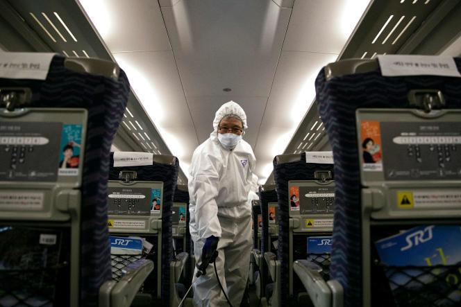 Un employé d'un service de nettoyage pulvérise du désinfectant dans un train dans le cadre de la propagation du nouveau virus, à Séoul, le 24 janvier.