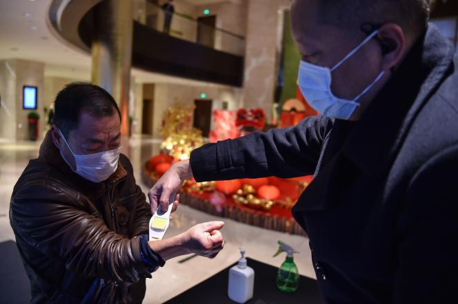L'employé d'un hôtel prend la température d'un client qui vient d'arriver à Wuhan, le 24 janvier.