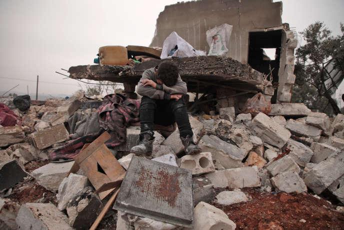 Un garçon syrien assis sur les décombres de la maison où il vivait avec sa famille déplacée dans le village de Kafr Taal, à l'ouest d'Alep (Syrie), après un bombardement, le 20 janvier 2020.