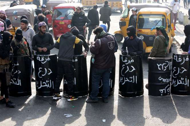 Des manifestants montrent des boucliers sur lesquels ont été inscrits les mots« brigade de protection de Tahrir», le 25 janvier à Bagdad.