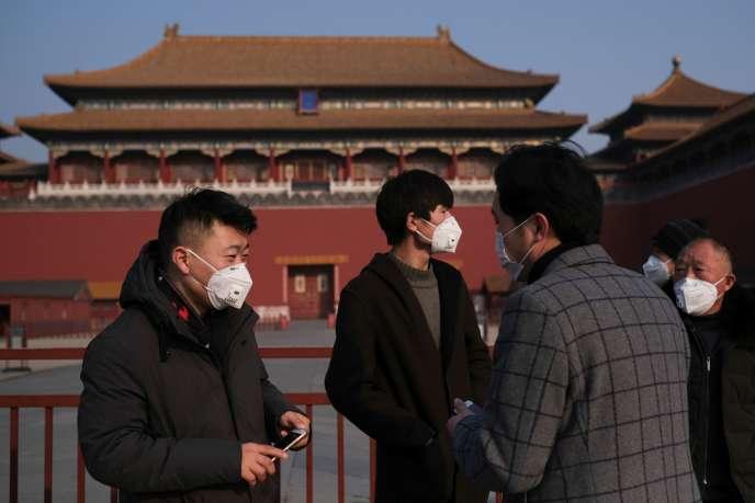 Des hommes portent des masques de protection à Pékin, le 25 janvier.